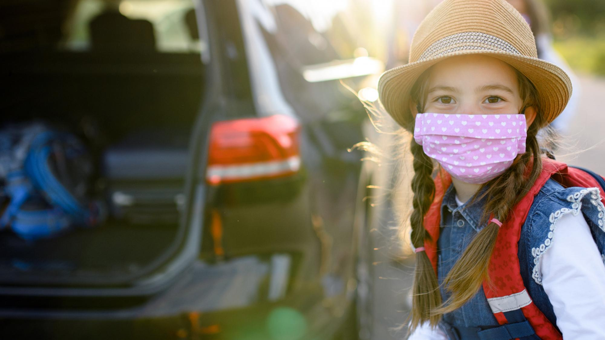 Young girl with pink face mask next to vehicle