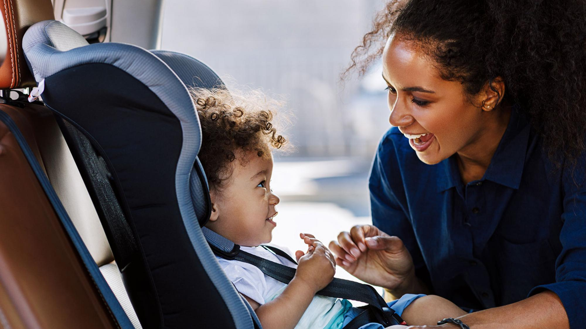 Woman putting baby in car seat and smiling