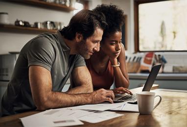 mixed race couple using laptop and reviewing their finances, rebuilding budget, financial review, financial setback