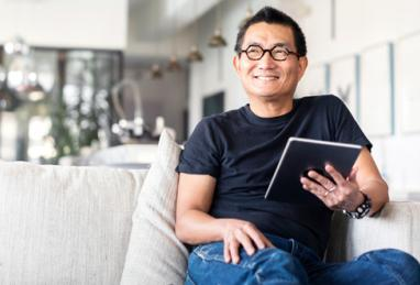 A happy man sitting on a couch holding his tablet smiling