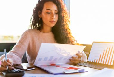 young woman sitting at table reviewing her investment portfolio, laptop, documents, investment reports, calculator, investing, wealth, building wealth