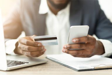 close-up of black business man holding credit card and smartphone, credit card, balance transfer, benefits of balance transfers