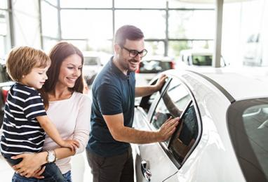 young family shopping for car at dealership, young white couple and son, car buying, buying a car, car buying cheat sheet, car buying tips, tips for buying a new