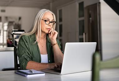 older woman with long gray hair sitting at table using laptop, online activity, online security, digital banking, fraud, scam, cybersecurity, account protection, tips